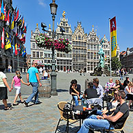Tourists sitting on terrace of pavement café on the Grote Markt / Main Square / Grand Place with view over the City Hall, guildhalls and the statue of Brabo in Antwerp, Belgium