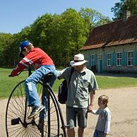 Tourists admiring old bicycle in front of traditional house in the open air museum Bokrijk, Belgium