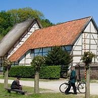 Rural constable and farmer in traditional costume in front of chapel, open air museum Bokrijk, Belgium