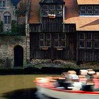Tourists in boat and wooden rear elevation along canal in Bruges, Belgium