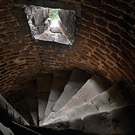 Narrow stone spiral staircase with loophole in the medieval Beersel Castle, Belgium