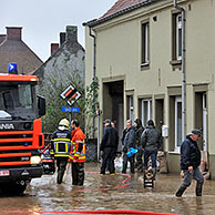 Flooded street and sandbags piled up in front of doors at Nederzwalm, Flanders, Belgium