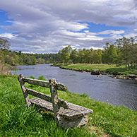 Old weathered wooden bench on riverbank along the river Spey in spring at Grantown-on-Spey, Highland, Moray, Scotland, UK