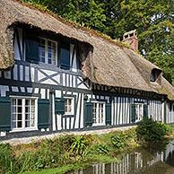 Timber-framed house with thatched roof along the river Veules, shortest river in France at Veules-les-Roses, Seine-Maritime, Normandy