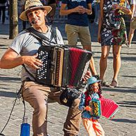 Busker / street performer with doll playing accordion during the Gentse Feesten / Ghent Festival, summer festivities at Ghent, Flanders, Belgium