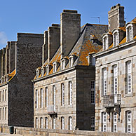 Tourists walking on the town ramparts and typical houses at Saint-Malo, Brittany, France