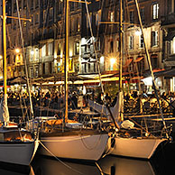 Sailing boats and tourists at pavement cafés / sidewalk cafes along the quay of the Honfleur harbour at night, Normandy, France <BR><BR>More images at www.arterra.be</P>