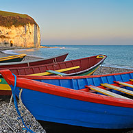 The Aval cliffs at sunset and colourful caïques, the wooden fishing boats at Yport, Normandy, France