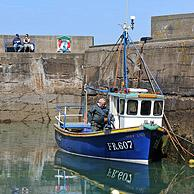 Fisherman on fishing boat in the Pennan harbor, a small coastal village in Aberdeenshire, Scotland, UK