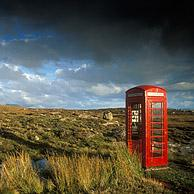 Red phone booth in heathland, Highlands, Scotland, UK