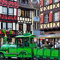 Colorful façades of timber framed houses and sightseeing train with tourists at Colmar, Alsace, France  <BR><BR>More images at www.arterra.be</P>