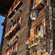House front of traditional wooden house / chalet decorated with old skis in the Alpine village Grimentz, Valais, Switzerland